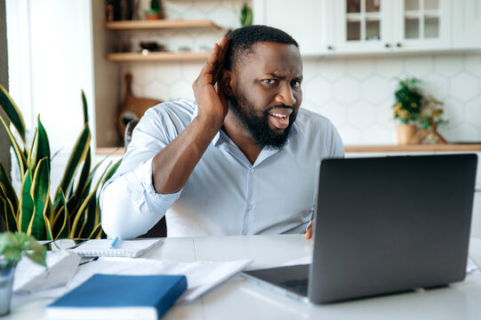 Afro american confused male freelancer or manager holding hand near ear, showing gesture of listening, while sitting at work desk and laptop, is listening news