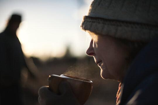 Senior woman having drink outside