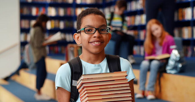 Middle eastern boy holding stack of books against multi colored bookshelf in library.