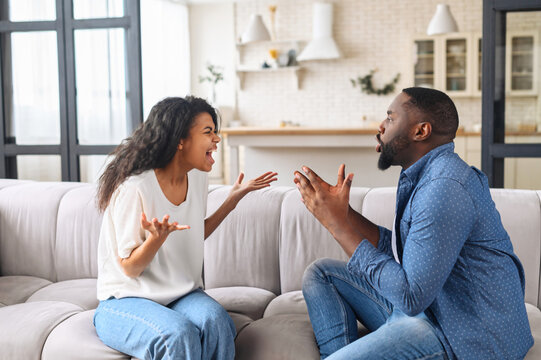 Multiracial couple is arguing at home. Angry young spouses screaming and misunderstanding to each other, African-American couple has relationships problem