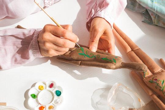 A woman designer will paint handmade dolls. Hobby.