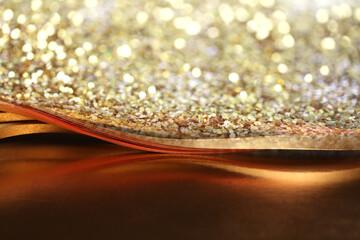 Abstract light blur blink sparkle defocus backgound. Gold (bronze) glitter shine dots confetti.