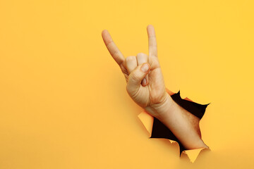 Male hand making a rock and roll gesture, party, goat on a yellow background