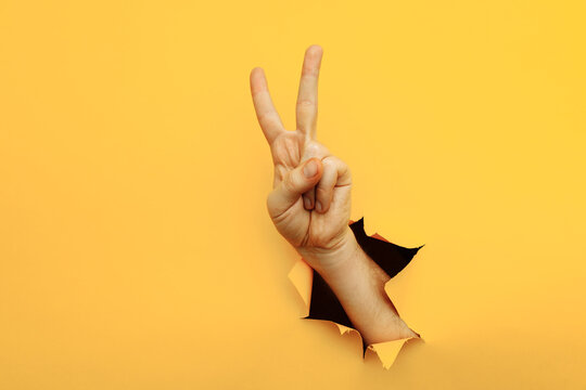 Hand showing peace gesture through torn yellow paper background. Victory, V sign