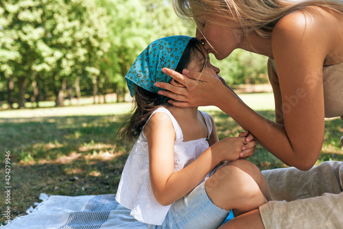Horizontal image of a mother kissing her pretty daughter on the forehead, sitting on the blanket on the grass in the park. Woman and her child having a summer picnic together. Happy Mother's day.