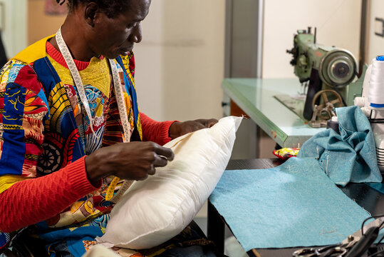 African textile industry artisan at work, tailor taking a measurement to create a pillow with wax fabrics typical of African culture, concept of small business and diversity