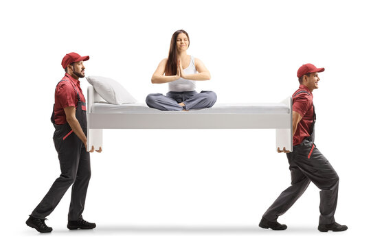 Young woman in pajamas sitting on a bed doing yoga and movers carrying the bed