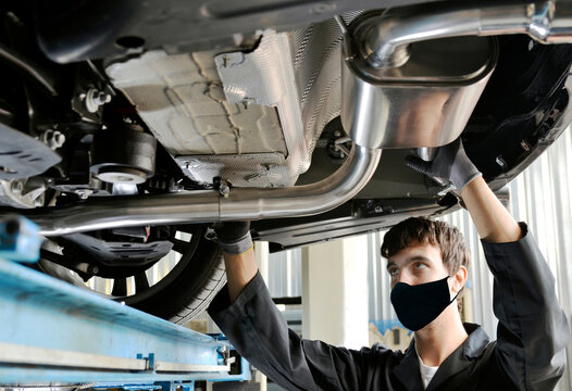 Young Mechanic With Protective Mask for Covid-19 virus on the Mouth Installing Exhaust Pipe Under a Car. New generation of sportive mufflers: double Car Exhaust Pipe chromed made of stainless steel