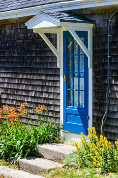 A charming blue door and gabled overhang on a shingle-side house welcomes walkers along the main road on Mohegan Island, Maine.  Copy space.