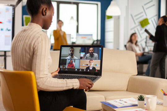 African manager woman discussing with remote colleagues using video call holding laptop sitting on couch in business modern office. Diverse coworkers planning new financial project in modern company