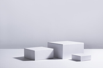 White square podiums in sunlight with shadow in white space. Showcase for cosmetic products, goods, shoes, bags, watches.