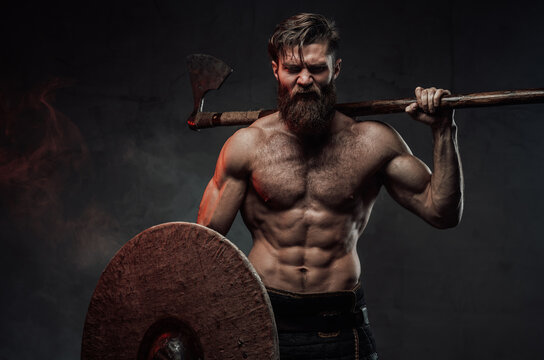 Frenzied viking in dark background with axe and shield