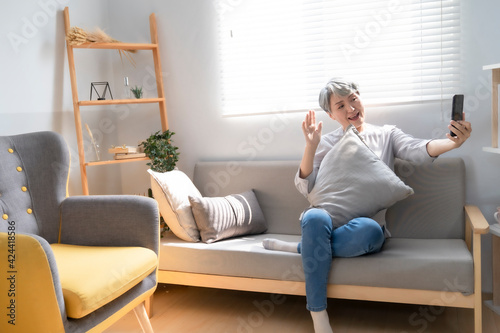 Elderly woman using smartphone video conference with grandchild while lying on sofa in living room at home. Enjoying time lifestyle senior family at home concept. Portrait looking at camera
