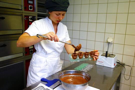 Confectioner apprentice Biondetti fills liquid chocolate into a mould to produce Easter bunnies at Eric's Confiserie Baumann in Zurich