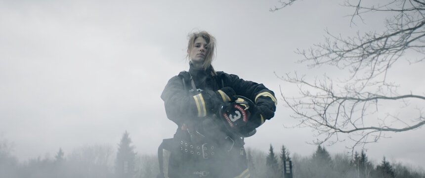 Hero shot, portrait of tired American female firefighter standing taking off her protective helmet, looking into camera