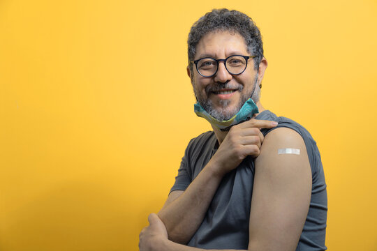 Handsome fifty years old man with lowered face mask showing arm with bandage after the coronavirus vaccination looking at the camera against an orange background. Mid aged people receiving vaccine