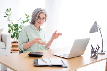Profile portrait of positive lady sit behind desktop look laptop hands explain speak have good mood indoors