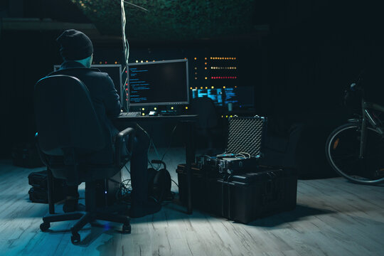 Shot from the Back a hooded hacker works on a computer with data displayed on screens in a secret hideout. In the background you can see monitors and temporary servers.