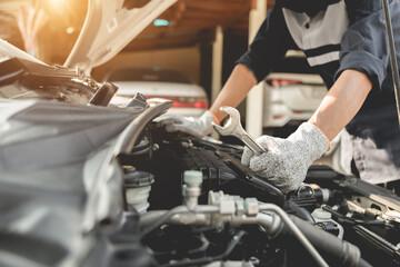 Fototapeta Automobile mechanic repairman hands repairing a car engine automotive workshop with a wrench, car service and maintenance,Repair service. obraz