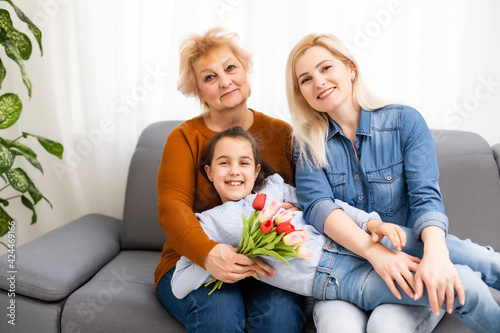 A little girl gives a bouquet of tulips to her mom and grandmother. They celebrate Mother's Day. They have a traditional family holiday.