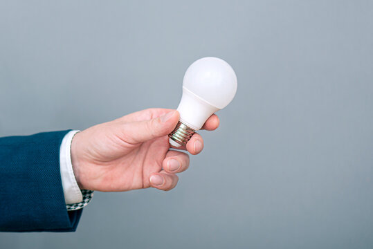 A man holding led light bulb in hand. Concept picture about economy, electricity and saving money