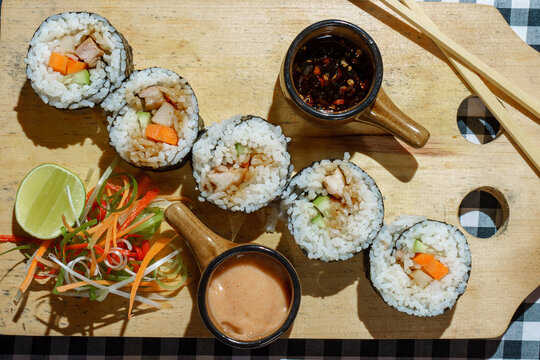 Overhead view of sushi maki rolls on a chopping board with chilli and spicy sauce