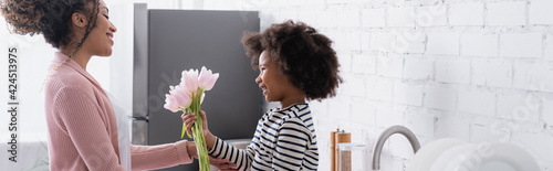 side view of african american child presenting fresh tulips to mom, banner