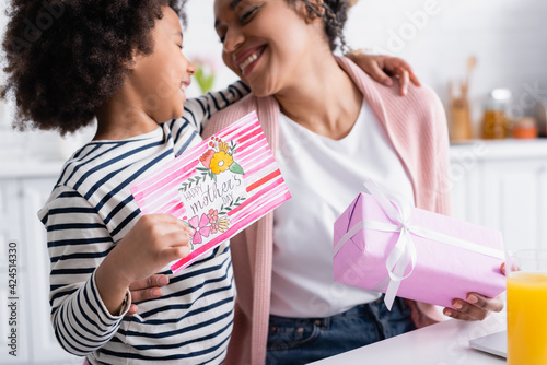 happy african american girl holding happy mothers day card near pleased mom on blurred background