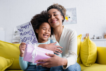 pleased african american woman holding gift box and embracing daughter with happy mothers day card
