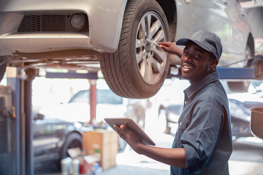 African maintenance male checking tire service via insurance system at garage with using tablet