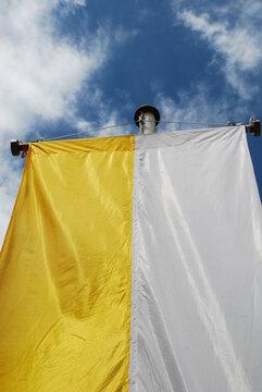 Die gelb, weiße Kirchenfahne der Katholischen Kirche wird an vielen Festtagen wie zur Erstkommunion, Firmung, Oster, Pfingsten und Weihnachten gehisst.