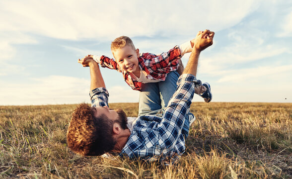 Happy family: father and son in nature in summer