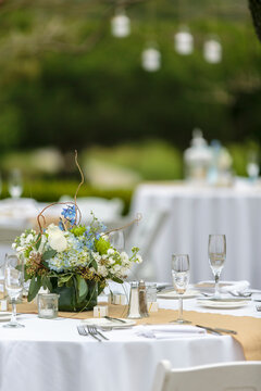 Tables set for an outdoor wedding reception in white, with blue flowers as decor