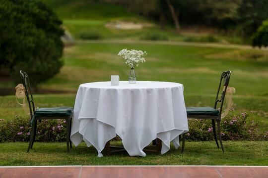 Wedding table with white linen for the bride and groom at an outdoor reception in a park setting