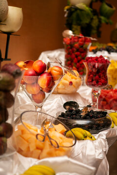 Catered table full of fruit in glass containers with peaches, prickely pears, strawberries, blackberries, melon and bananas for a wedding ceremony