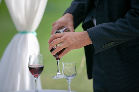 Man pouring wine into stem glasses in celebration of a wedding