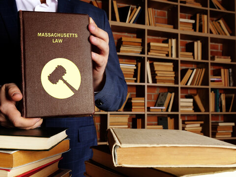 Jurist holds MASSACHUSETTS LAW book. Massachusetts residents are subject to Massachusetts state and U.S. federal laws