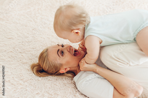 Mother's day. Woman playing with her newborn baby son at home. Family having fun lying on bed in bedroom.