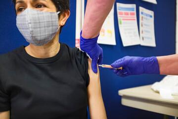 Obraz Asian woman getting Covid 19 vaccine injection, UK - fototapety do salonu