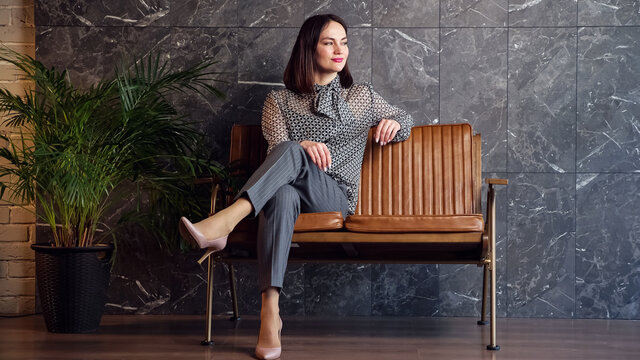 Young brunette in grey classic costume sits on brown bench near large green pot plant at marble wall in waiting room by new office