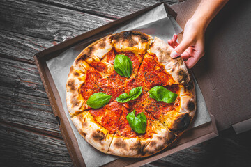 woman Hand takes a slice of Pepperoni Pizza with Mozzarella cheese, salami, Tomatoes, pepper, Spices and Fresh Basil. Italian pizza on wooden table background in box