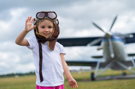 A cute little girl dressed in a cap and glasses of a pilot on the background of an airplane. The child dreams of becoming a pilot.