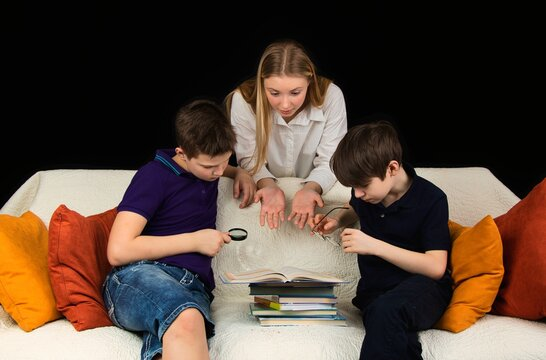Children sitting on the couch are looking at a book and discussing a school assignment.