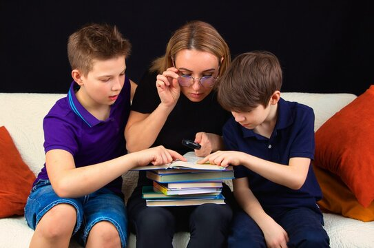 Children with a teacher are sitting on the couch, discussing a school assignment, close-up on.
