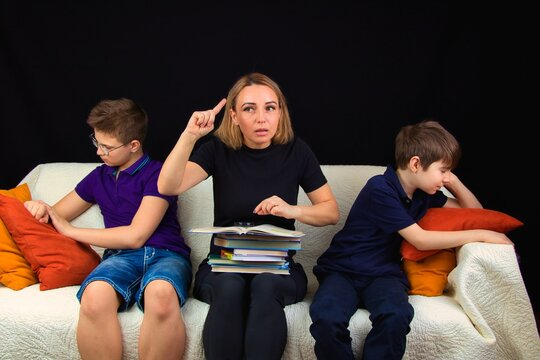 Children with a teacher are sitting on the couch and do not want to learn a school assignment.