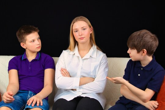 Children are sitting on the couch, discussing a school assignment, close-up.