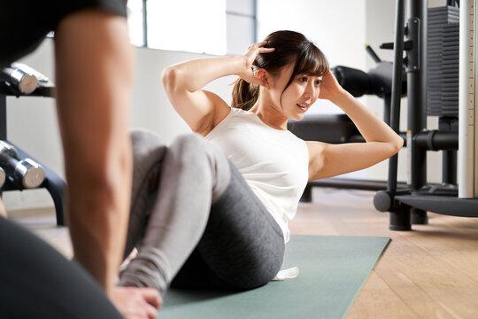 パーソナルトレーナーの指導で腹筋運動をするアジア人女性