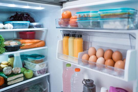 open fridge door with full of food and ingredient inside