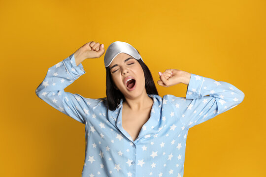 Young tired woman with sleeping mask yawning on yellow background
