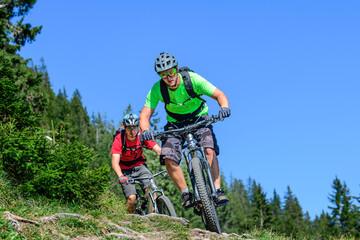 Fototapeta Zwei junge Radsportler auf dem Mountainbike auf einem verwurzelten Single-Trail obraz
